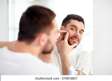 beauty, hygiene, skin problem and people concept - young man looking to mirror and squeezing pimple at home bathroom