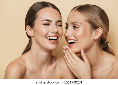 Beauty image of amazing optimistic beautiful blonde and brunette women posing naked isolated over beige wall background talking with each other laughing.