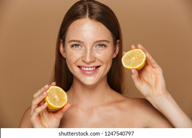 Beauty image of pretty shirtless woman with long hair holding two pieces of orange isolated over beige background