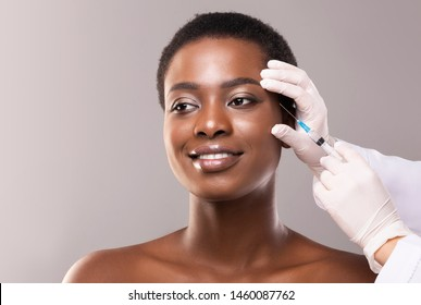 Beauty injection. Beautiful black woman making plastic surgery procedure for face