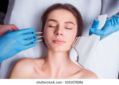 Beauty Injection. Closeup Of Doctor Hands With Syringe Near Female Face. Portrait Of Beautiful Woman Receiving Facial Skin Lifting Treatment.