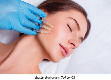 Beauty Injection. Closeup Of Doctor Hands With Syringes Near Female Face. Portrait Of Beautiful Woman Receiving Facial Skin Lifting Treatment.