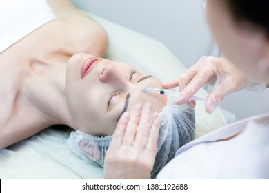 Beauty injection for female face. Cosmetician sets filler in forehead, close up, selected focus. Beauty service, face lifting, rejuvenation, biorevitalization, cosmetic surgery, mezotherapy, anti