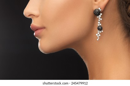 beauty and jewelery concept - woman wearing shiny diamond earrings