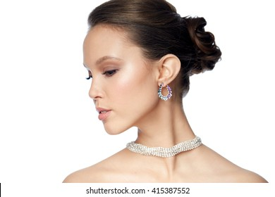 beauty, jewelry, accessories, people and luxury concept - close up of beautiful asian woman face with earring