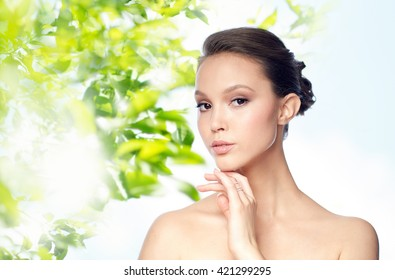 beauty, jewelry, accessories, people and luxury concept - face of beautiful young asian woman with golden ring over green natural background