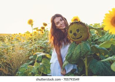 Beauty joyful girl with sunflower enjoying nature on sunset sunflower field