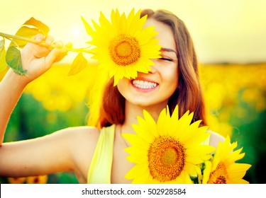 Beauty joyful teenage girl with sunflower enjoying nature and laughing on summer sunflower field. Sunflare, sunbeams, glow sun. Backlit