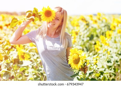 Beauty joyful teenage girl with sunflower enjoying nature and laughing on summer sunflower field. Sunflare, sunbeams, glow sun. Backlit