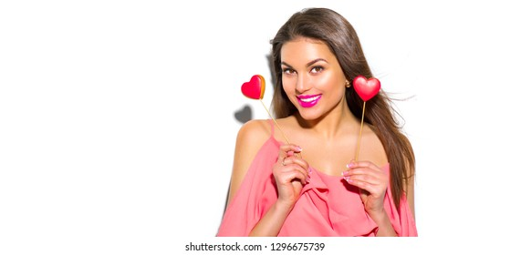 Beauty joyful Young fashion model Girl with Valentine Heart shaped cookies in her hands. Love Concept. Beautiful smiling young woman. Valentines Day gift. Isolated on white background