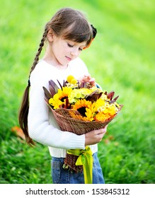 Beauty kid girl with bouquet of sunflowers and yellow flowers