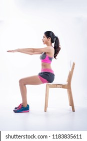 The beauty lady iis wearing exercise suit,sitting on wooden chair,raise hands up in the air,sit upright,basic pattern for exercise and balancing