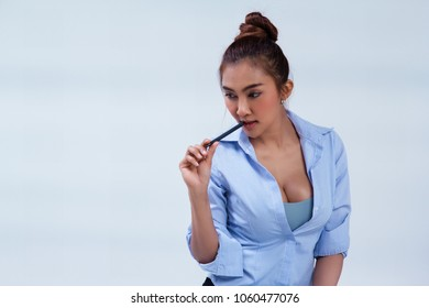 The beauty lady is wear blue shirt,she is put black to touch her lip,thinking about work,office hour