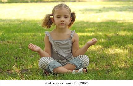 beauty little girl meditating in park