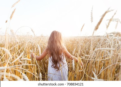 Beauty little girl outdoors enjoying nature wheat field. Beautiful girl in white dress running on the autumn field at sunset light.