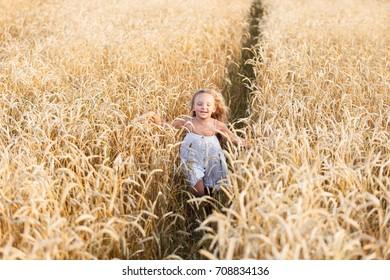 Beauty little girl outdoors enjoying nature wheat field. Beautiful girl in white dress running on the autumn field at sunset light.