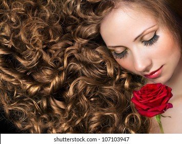 Beauty with long curly hair and red rose