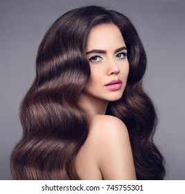 Beauty long wavy hair. Elegant Brunette girl portrait with healthy shiny hairstyle. Beautiful model with makeup isolated on studio dark background. Shampoo care product.