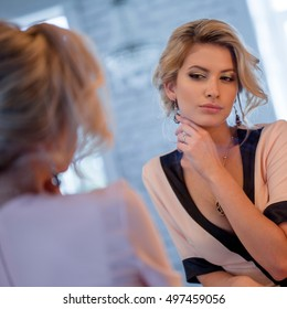 Beauty luxury blonde woman. Attractive young model in beautiful dress sitting in front of mirror, to primp