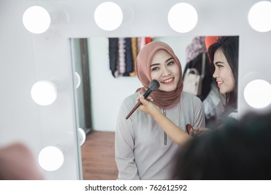 Beauty make up artist applying cosmetic. Girl gets blush on the cheekbones