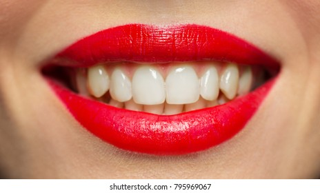 beauty, make up and people concept - close up of smiling woman lips or mouth with red lipstick