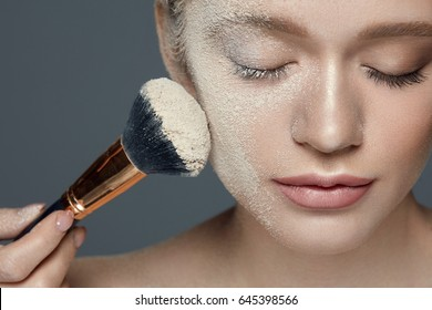 Beauty Makeup. Beautiful Female Model With Closed Eyes Putting Loose Make-up Powder With Cosmetic Brush On Skin. Closeup Of Young Woman Face Covered With Cosmetic Powder Product. High Resolution
