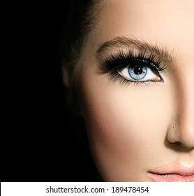 Beauty makeup for blue eyes. Part of beautiful face closeup. Perfect skin, long eyelashes. Make up concept. isolated on black background