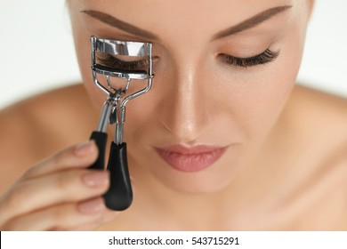 Beauty Makeup. Closeup Of Beautiful Female Model Face With Professional Natural Make-up And Smooth Soft Skin. Young Woman Using Eyelash Curler On Long Eyelashes. Curly Eye Lashes. High Resolution