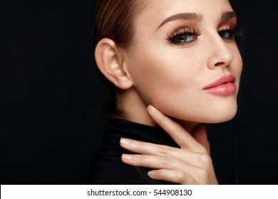 Beauty Makeup. Closeup Of Beautiful Smiling Woman Touching Soft Smooth Facial Skin. Portrait Of Sexy Young Female Model With Professional Make-up And Long Black Eyelashes. Cosmetics. High Resolution