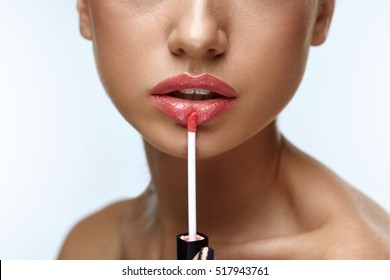 Beauty Makeup. Closeup Of Beautiful Woman Face With Smooth Skin, Soft Plump Full Lips With Lip Gloss On. Close-up Of Girl Applies Liquid Lipstick Or Lip Balm, Lip Care Cosmetics. High Resolution Image