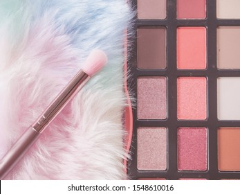 Beauty and Makeup concept from facial cosmetics, blush brush, highlighter palette and eye shadows with pink-tone for face make up on pink background.