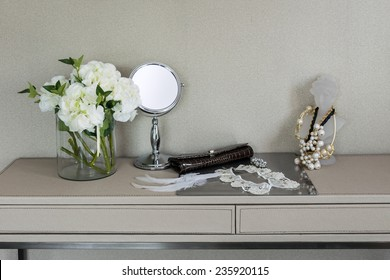Beauty and make-up concept: mirror,jewelry and makeup set on a table