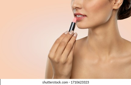 beauty, makeup and cosmetics concept - happy smiling young woman with pink lipstick over beige background