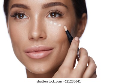 Beauty Makeup Cosmetics. Portrait Of Beautiful Young Woman With Healthy Clean Skin And Perfect Facial Make-up. Closeup Of Attractive Sexy Female Applying Concealer On Skin Under Eyes. High Resolution