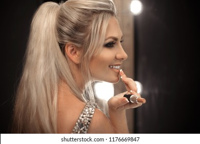 Beauty makeup. Fashion glamour portrait of sexy blonde woman with long ponytail hair style holding beige lipstick by mirror bulbs at dressing room. Beautiful face over dark. Make up product cosmetics