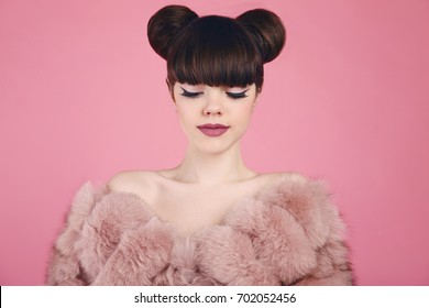 Beauty makeup. Fashion teen girl model in fur coat. Brunette with matte lips and bun hairstyle posing over studio pink background.