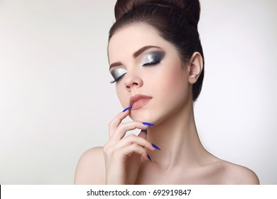 Beauty makeup girl. Matte lipstick. Manicure nail. Young fresh brunette with glitter eyeshadow isolated on studio background.