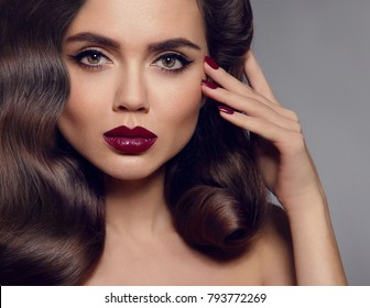 Beauty makeup. Glamour woman face close up. Manicured nails. Healthy shiny hairstyle. Fashion shiny highlighter on skin, sexy gloss lips make-up and dark eyebrows. Vogue style photo