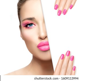 Beauty Makeup and Nail Art Concept. Beautiful fashion model girl with pink makeup, perfect skin and trendy pink nails, half face with a white card template. High fashion portrait isolated on white