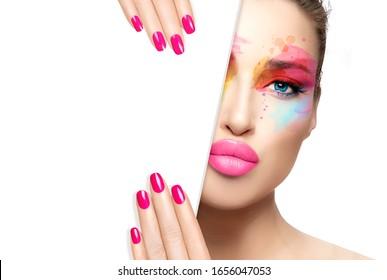 La maquillaje de belleza y el concepto de arte de las uñas. Hermosa modelo chica con maquillaje colorido, piel perfecta y uñas rosas a la moda, media cara con una plantilla de tarjeta blanca. Retrato de alta moda aislado en blanco