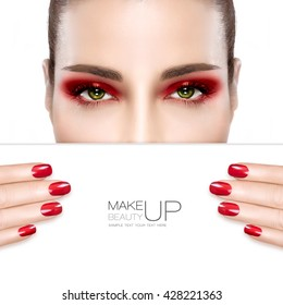 Beauty Makeup and Nail Art Concept. Beautiful fashion model woman with red smoky eye makeup to match her manicured nails, foundation on a unblemished skin, half face with a white card template.