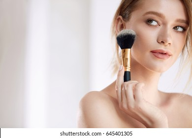 Beauty Makeup. Portrait Of Beautiful Young Female Model With Cosmetic Brush In Hand. Closeup Sexy Young Woman With Perfect Soft Skin And Fresh Natural Makeup Applying Powder On Face. High Resolution