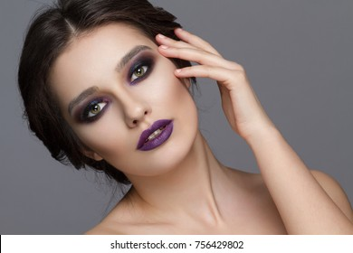 Beauty makeup in the studio on a grey background . Smoky eyes and violet lips makeup