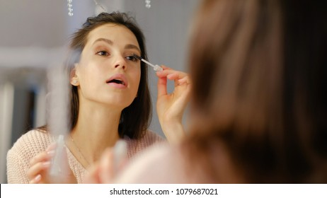 beauty makeup tutorial blog. vogue glamour fashion lifestyle. young beautiful girl applying mascara to eyelashes in front of the mirror
