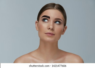 Beauty makeup. Woman coloring eyebrow with gel tint portrait. Girl model setting liquid peel-off brow gel on eyebrow