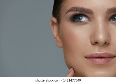 Beauty makeup. Woman face with beautiful eyes and eyebrows make-up and long black eyelashes closeup