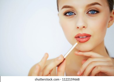 Beauty and Makeup. A Woman With Pure Skin and Blue Eyes. Beautiful Young Girl Draws Lips With A Pencil. Skin Care. High Resolution