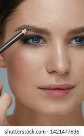 Beauty makeup. Woman shaping eyebrow with brow pencil closeup. Girl model with professional makeup contouring eyebrows