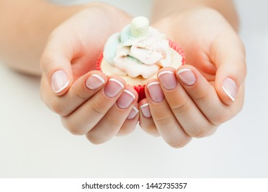 Beauty manicure. Woman's hands with nails holding puncake