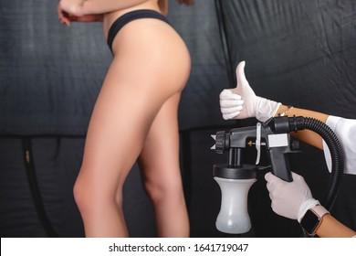Beauty master applying fake tan on woman`s body. Ekotanning. Ecological tan. Female making tanning in tan studio. Client making an express bronzing by airbrush-pistol.